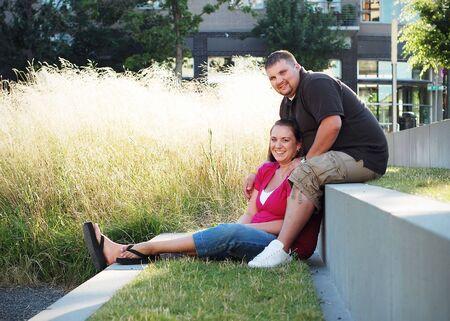 幸せなカップルの笑顔します。外背景のマンションで装着されています。水平方向に組み立てられた写真。
