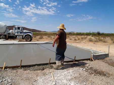 Construction worker smoothing out a freshly poured concrete slab. Shot is set in a desert with a white cement truck in the background. Horizontally framed shot. Stock Photo - 3418465