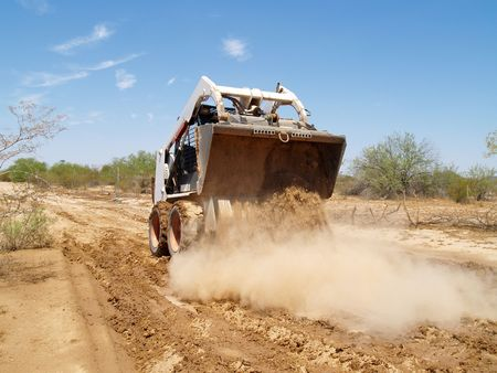 Construction worker driving a skid steer loader and dumping his payload at a desert construction site. Horizontally framed shot.