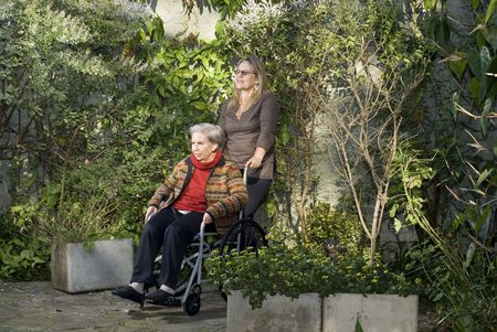 A younger woman is with her elderly mother in a garden.  She is pushing her wheelchair, and they are both looking straight ahead.   Horizontally framed shot. photo