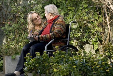 A younger woman is with her elderly mother in a garden.  She is smiling at the woman who is holding tablet and a pen, and looking back at her.   Horizontally framed shot.