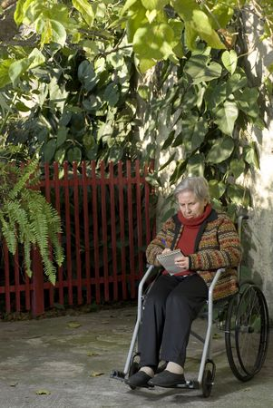 An elderly woman sitting in a wheelchair is in a garden.  She is writing something on a notepad and looking down at it.  Vertically framed shot. photo
