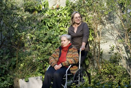 A younger woman is with her elderly mother in a garden.  She is pushing her wheelchair, smiling, and they are both looking away from the camera.   Horizontally framed shot. photo