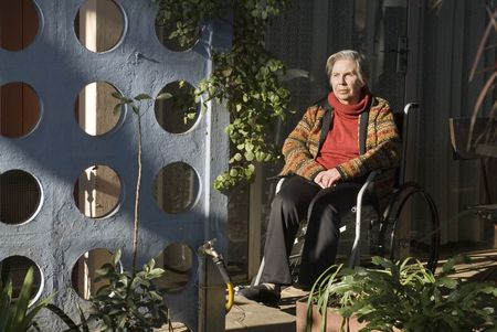 An elderly woman is sitting in a wheelchair in her garden.  She is staring off into the distance.  Horizontally framed shot. photo