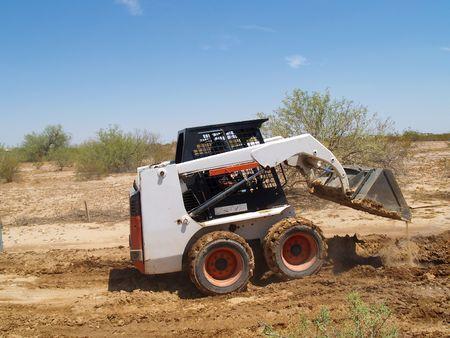 skid steer: Construction worker driving a skid steer loader at a desert construction site. Horizontally framed shot. Stock Photo
