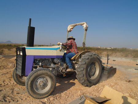 Man on tractor looking backwards as he works. Horizontally framed shot. Stock Photo - 3418443