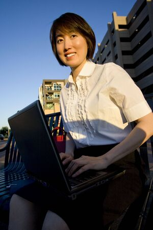 vertically: Smiling woman works on laptop while smiling at camera. Vertically framed photo. Stock Photo