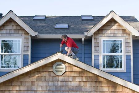 reparaturen: Man arbeitet mit einem Bohrer auf einem Dach. Horizontal gerahmte Foto.