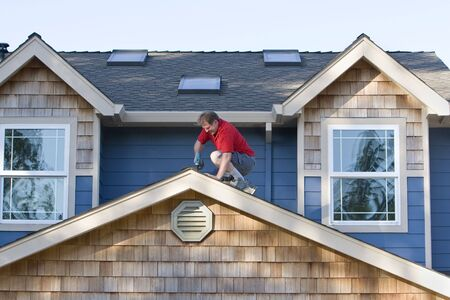 home repairs: Man working with a drill on a roof. Horizontally framed photograph.