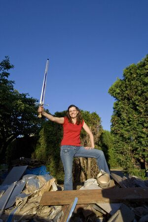 joking: Woman joking around as she stands on top of a pile of garbage holding a sword. Vertically framed photo. Stock Photo