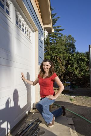 crouches: Woman smiling as she crouches next to her garage. Vertically framed photo. Stock Photo