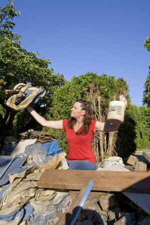 Woman looking frustrated as she stands in a pile of rubble and holds up garbage. Vertically framed photograph Stock Photo - 3440425