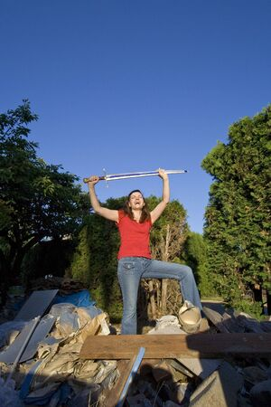 Woman joking around as she stands on top of a pile of garbage holding a sword. Vertically framed photograph. photo
