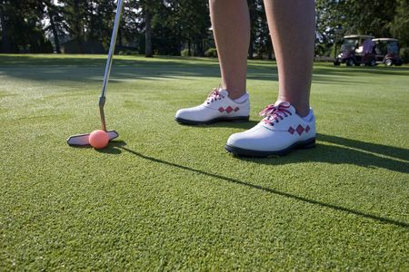 A person is standing on the green of a golf course.  They are about to putt a ball into a hole.  Horizontally framed shot. photo
