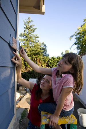 Mother showing her daughter where to apply paint as they paint their house. Vertically framed photograph. photo