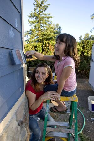 Mom and daughter smiling and playing as they paint the house and each other's noses. Vertically framed photo photo