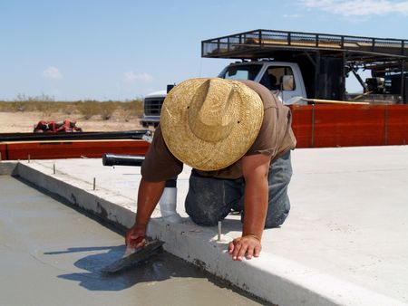 concrete: Shot of a construction worker smoothing out a freshly poured concrete slab using a hand trowel. Horizontally framed shot. Stock Photo