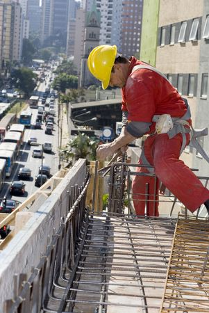 vertically: Worker installs rebar on top of building under construction. Vertically framed photo. Stock Photo