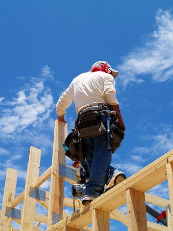 worksite: Construction worker standing on a  frame with a tool belt. Vertically framed photo. Stock Photo