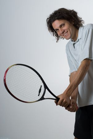 vertically: Athlete holding a tennis racket.  He is smiling and looking at the camera.  Vertically framed shot. Stock Photo