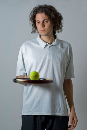 vertically: Male athlete holding a tennis racket and balancing a ball on it.  He is looking at the tennis ball.  Vertically framed shot. Stock Photo