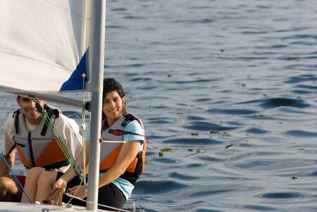 若いカップルは一緒に湖でセーリングします。 彼らはカメラを見ています。 水平方向にフレーム ショット。