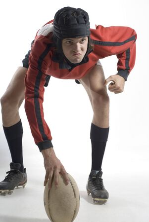 A rugby player is posing inside a studio.  He is dressed in a rugby uniform, holding a football, and looking away from the camera.  Vertically framed shot. photo
