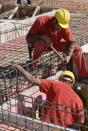 rebar: Construction workers install rebar during building construction. Vertically framed photo.