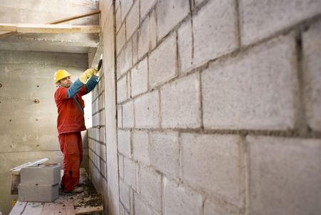builds: Construction worker builds cinder block wall while standing on scaffolding. Horizontally framed photo.