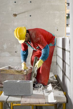 vertically: Construction worker bends to mix cement while building cinder block wall. He is wearing an orange suit and a yellow hat. Vertically framed photo. Stock Photo