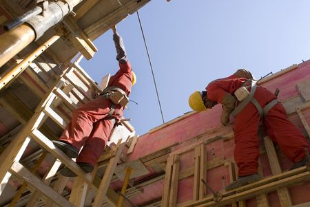 worksite: Construction workers build new wall for building under construction. They are standing on scaffolding and a ladder. Horizontally framed photo. Stock Photo