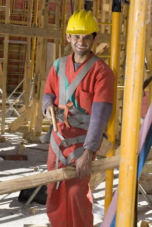 vertically: Construction worker saws board with handsaw while smiling at camera. Vertically framed photo. Stock Photo