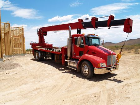Red semi truck with a crane on it in a construction site with a  frame in the background. Horizontally framed photo. Stock Photo