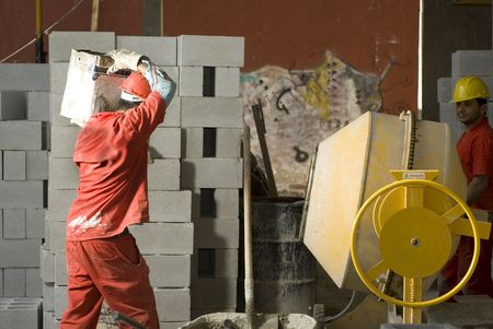 horizontally: Construction worker caries construction material on shoulder. Horizontally framed photo. Stock Photo