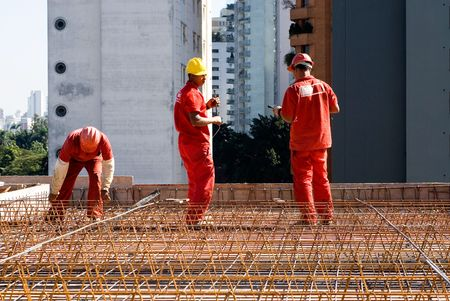 constrution: Constrution workers working among rebar to build new building. Horizontally framed photo.