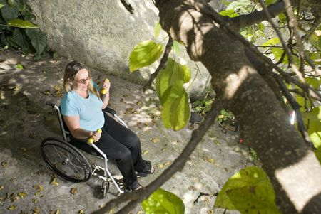 Woman sits in wheelchair beneath tree. She is lifting weights and looking forward. Horizontally framed photo. photo