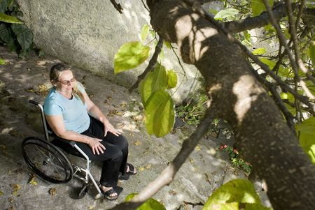 Woman sits outdoors in a wheelchair smiling straight ahead. Photo is taken from above. Horizontally framed photo. photo