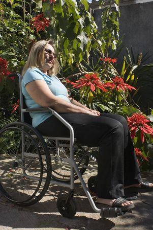 Woman in blue shirt reclines in wheelchair next to flowery bush. She is wearing sunglasses and looking ahead. Vertically framed photo. photo