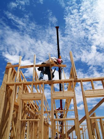 Construction site with scaffolding, a crane, and a construction worker standing on some scaffolding. Vertically framed photo. Stockfoto