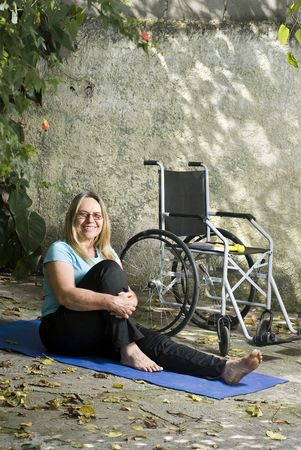 Woman sits next to a wheelchair on blue yoga mat outdoors. Her arms are around her bent knee with other leg extended. Horizontally framed photo. photo