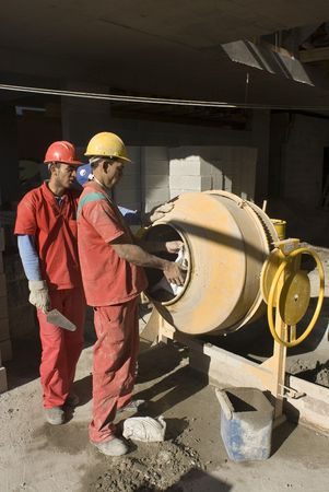 Construction workers work with cement mixer to mix cement for new construction. They are wearing orange suits, hard hats and one is holding a trowel. Vertically framed photo.