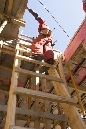 vertically: Construction worker stands on ladder. Photo taken from below. Vertically framed photo.