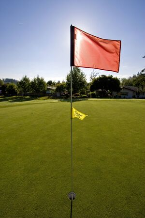 blocking: View of a golf course as the sun is going down.  The flag is blocking the sun.  Vertically framed shot. Stock Photo