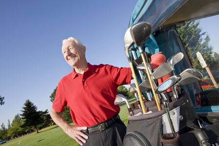 An elderly man is standing next to a golf cart on a golf course.  He is smiling and looking away from the camera.  Horizontally framed shot. Stock Photo