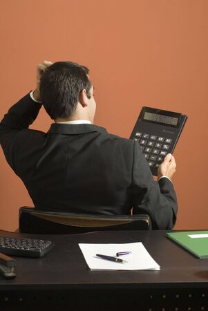 vertically: Businessman scratches his head as he looks at his calculator at his desk. Vertically framed photo.