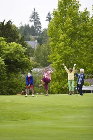 Group of four women celebrating with their arms up while playing golf. Vertically framed photo.