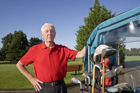 he: An elderly man is standing next to a golf cart on a golf course.  He is smiling at the camera.  Horizontally framed shot.