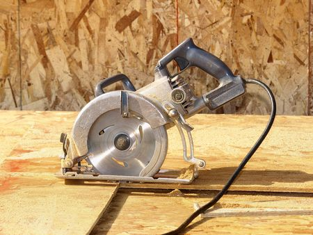 worksite: Power sander saw standing on plywood. Horizontally framed photo.