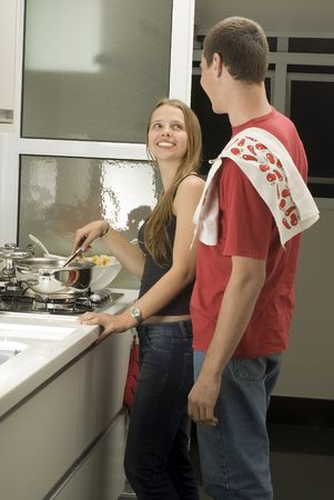 Man and woman stand in kitchen smiling at eachother. Woman stirs and man has towel over shoulder. Vertically framed photo.