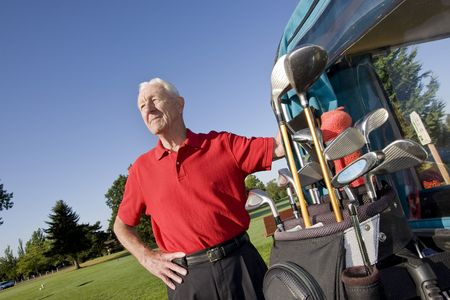 An elderly man is standing next to a golf cart on a golf course.  He is smiling and looking away from the camera.  Horizontally framed shot. Imagens